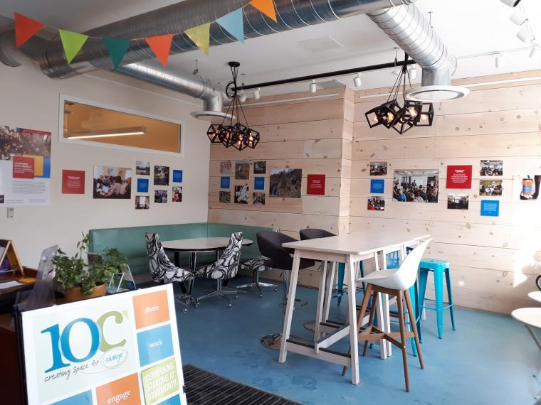 Photo showing the 10C lobby downtown Guelph. On the far walls, we see the photos and text forming the exhibit on community engaged learning.