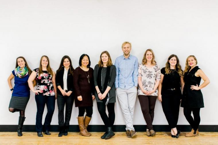 All 9 CESI staff members pose in front of a white wall