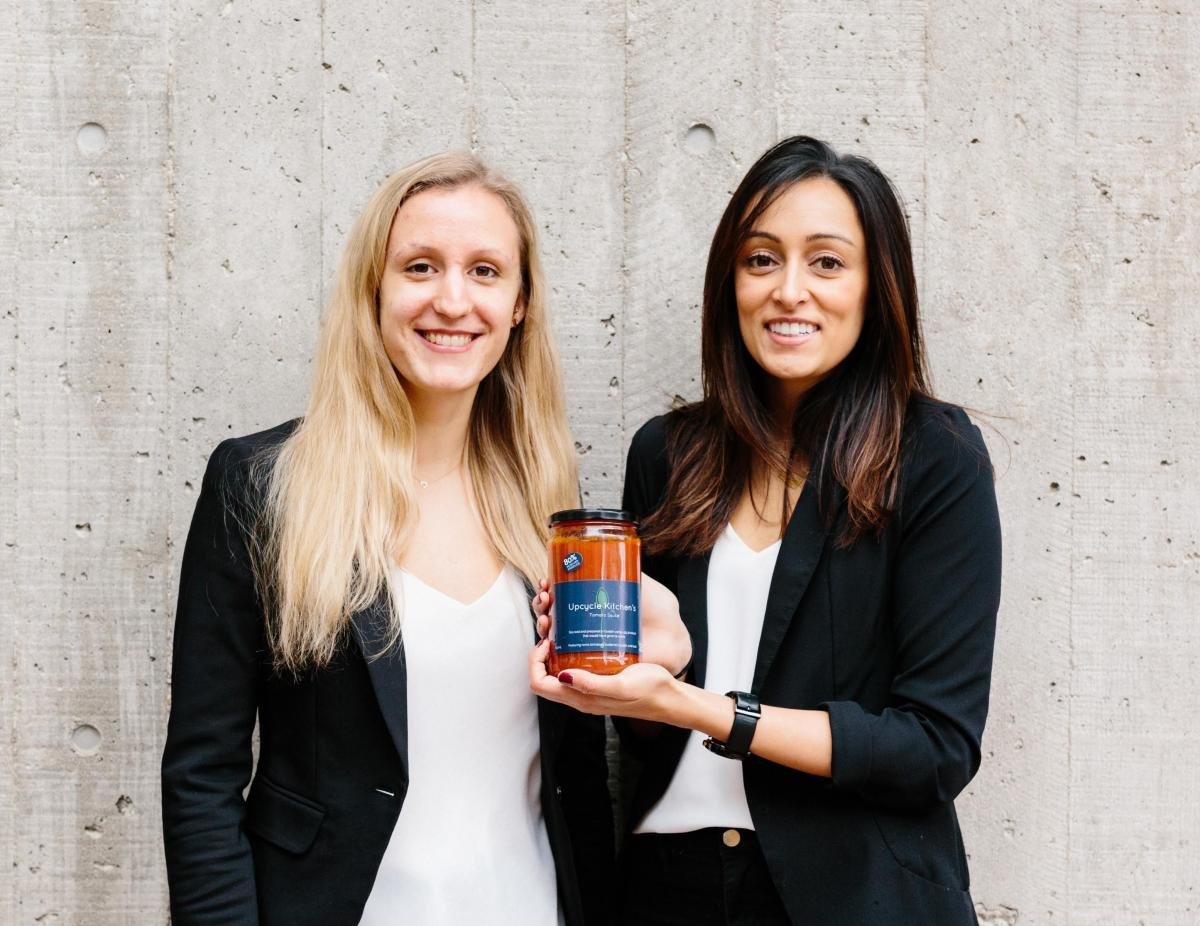 Photo of Laura Frielingsdorf and Kiran Bains holding a jar of Upcycle Kitchen tomato sauce.
