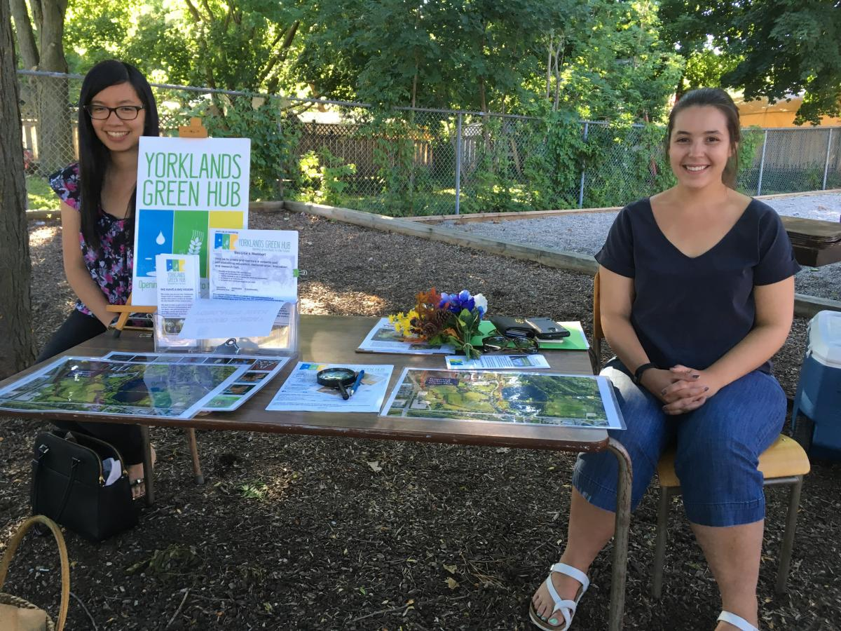 Photo of two Research Shop students sitting at a kiosk representing the Yorklands GreenHub.