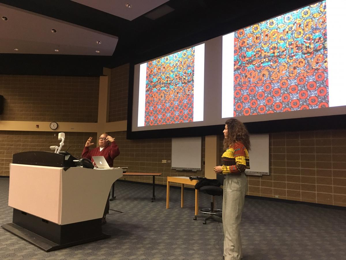 Photo showing Syrus Ware, artist and activist, presenting in Saba Safdar's Social Psychology class. The picture shows Syrus, Saba, and a large screen with a picture of colourful art. Students are not visible on the image.
