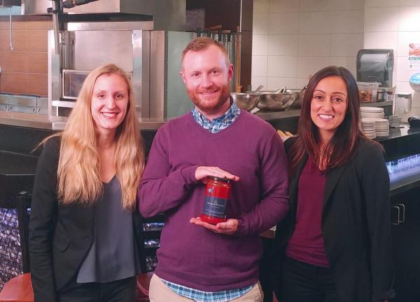 Photo of Laura Frielingsdorf, Tom Armitage and Kiran Bains holding a jar of tomato sauce.